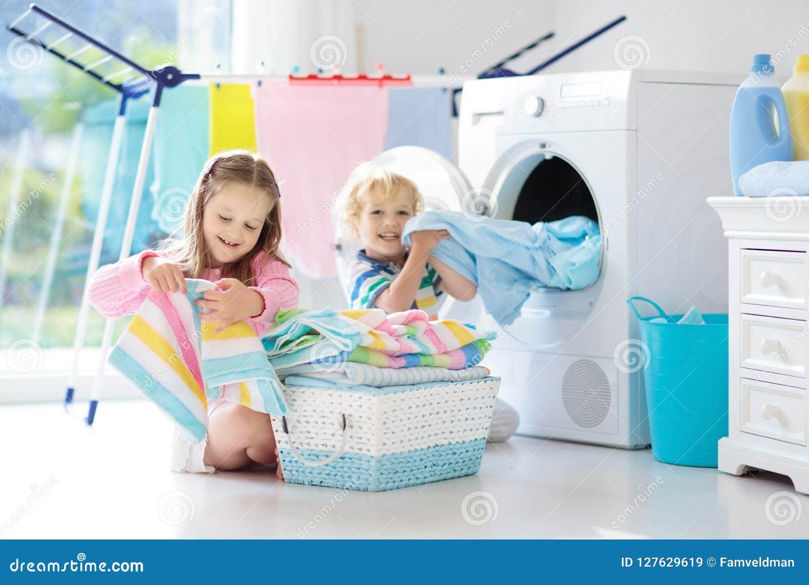 Niños en lavadero con la lavadora