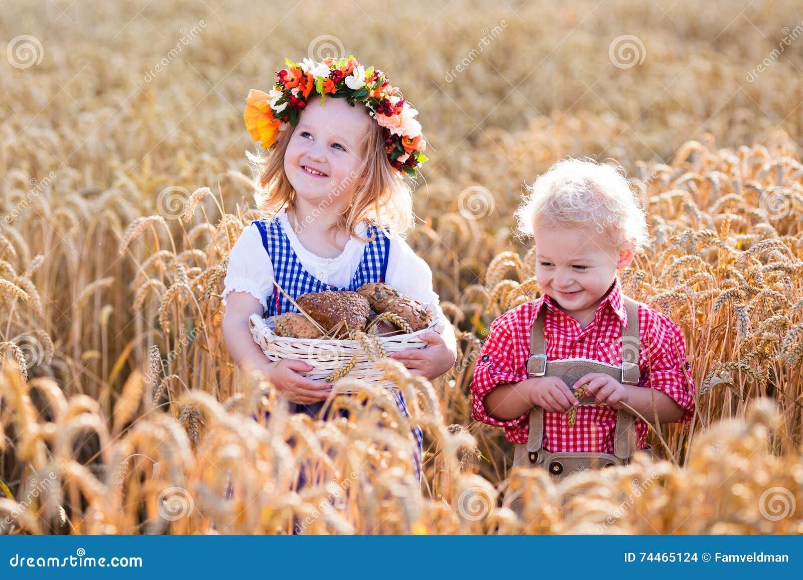 Niños en trajes bávaros en campo de trigo
