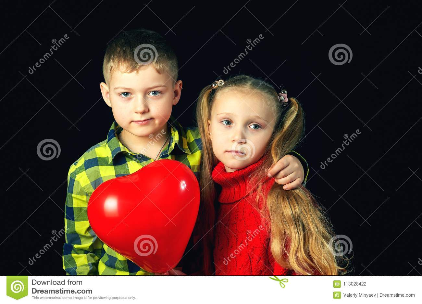 Niños en un fondo oscuro Muchacho y muchacha con el globo rojo