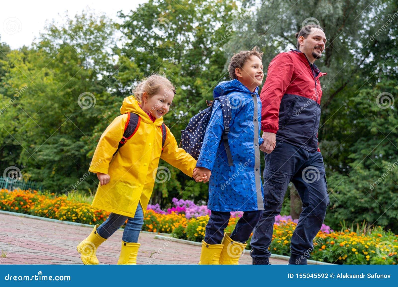 Niños felices con risa de la alegría de ir a enseñar, vestido en impermeables, con una cartera detrás de la mochila