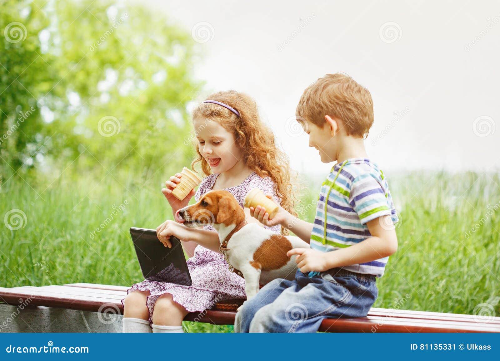 Niños felices con un perro de perrito del amigo que juega en la tableta
