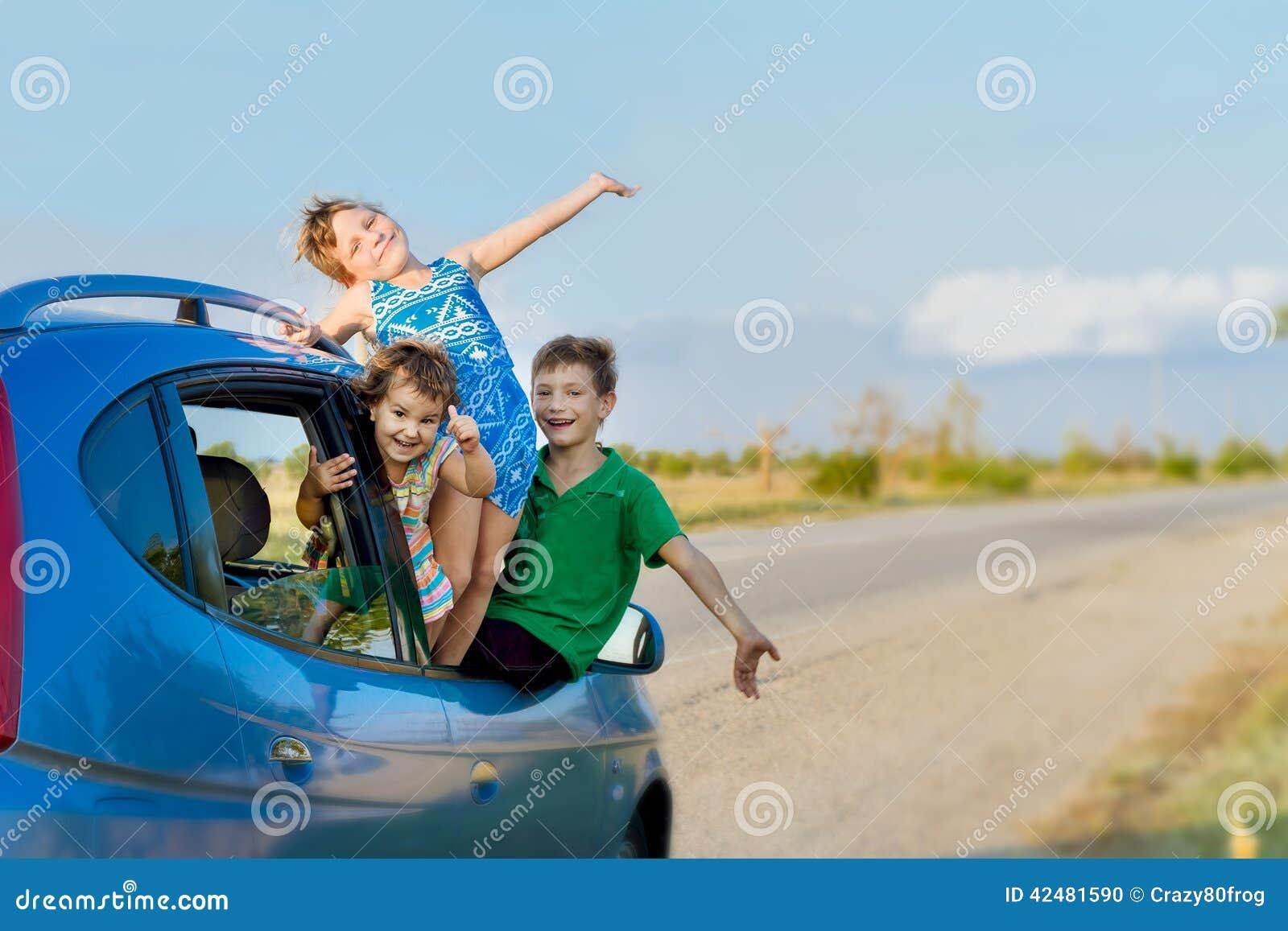 Niños felices en el coche, viaje de la familia, viaje de las vacaciones de verano