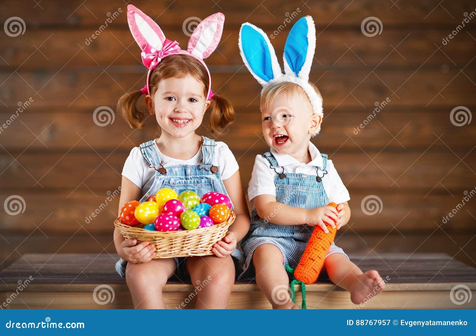Niños felices muchacho y muchacha vestidos como conejitos de pascua con la cesta de
