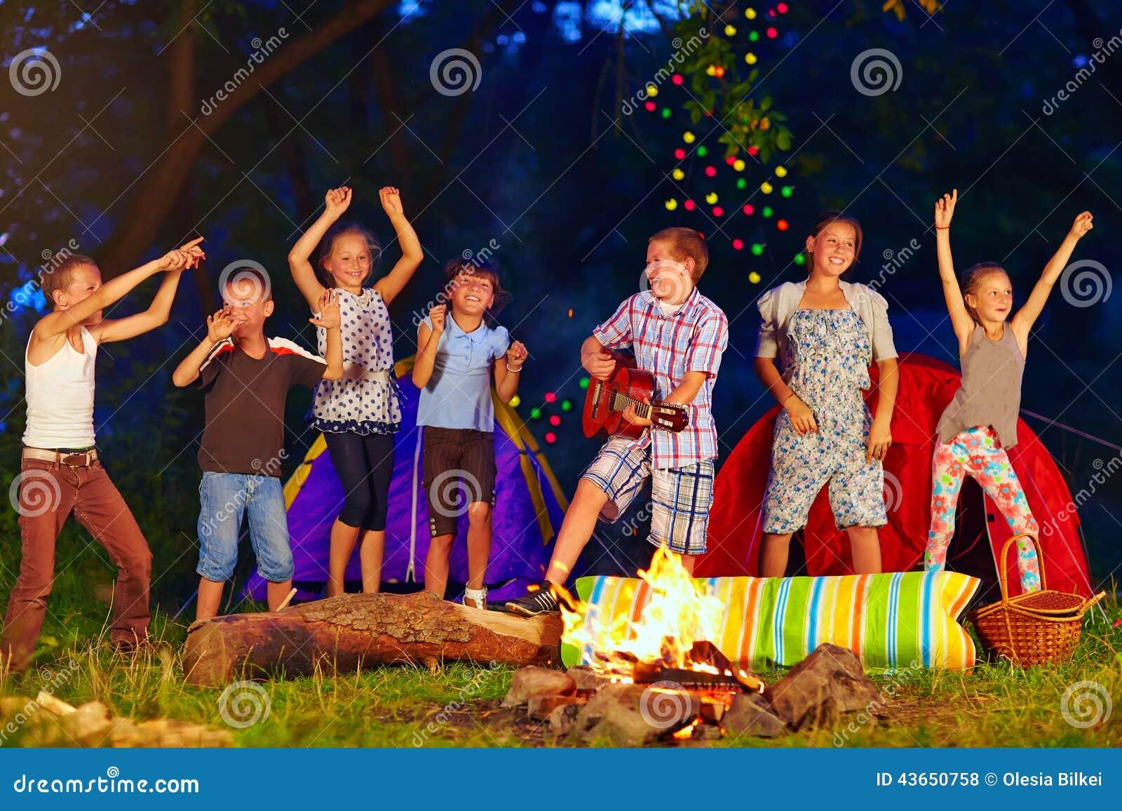 Niños felices que bailan alrededor de hoguera