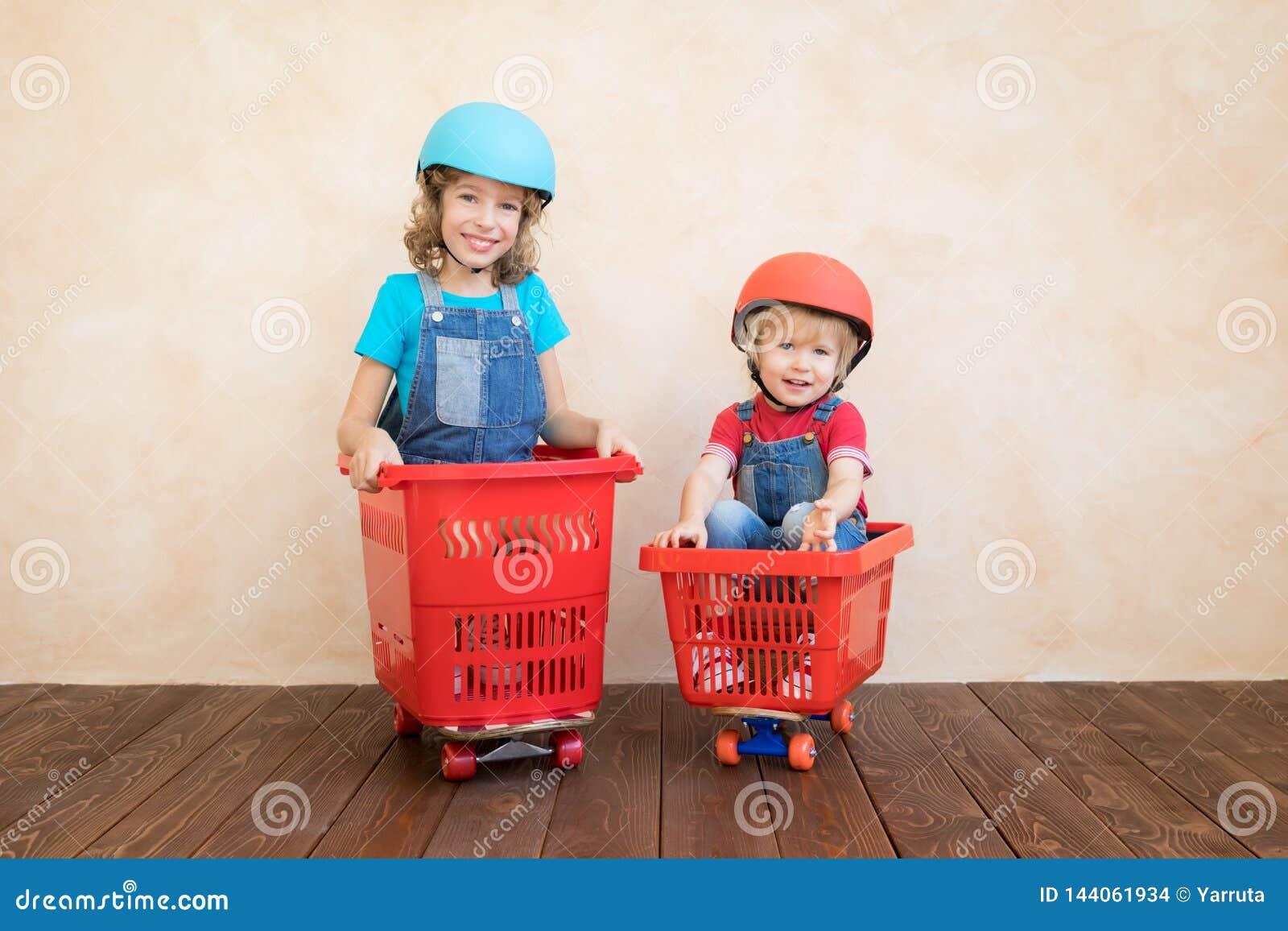 Niños felices que conducen el coche del juguete en casa