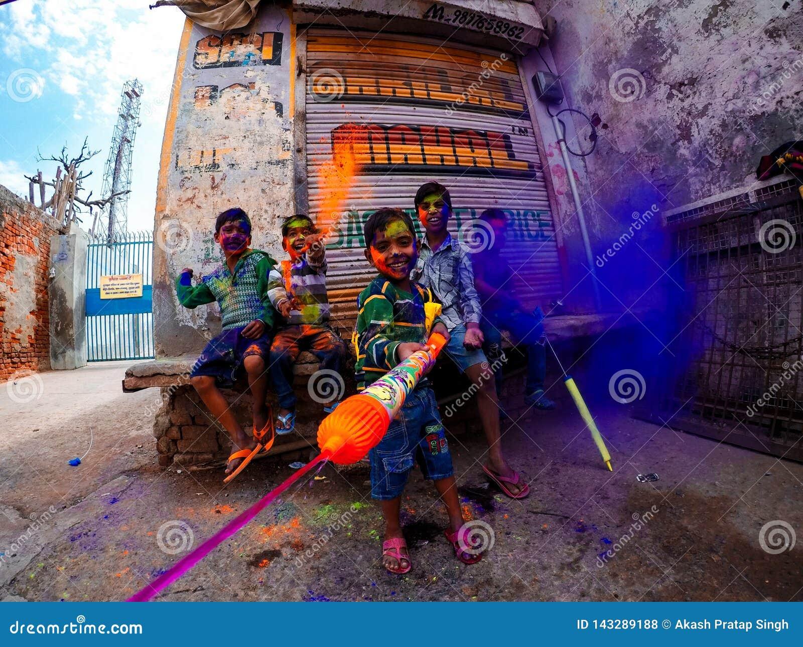 Niños felices que juegan holi en la India