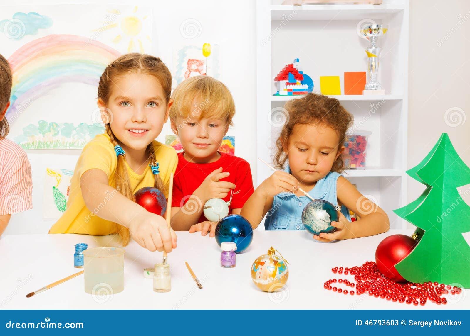Niños Felices Que Pintan Las Bolas Del Año Nuevo Para El árbol De ...