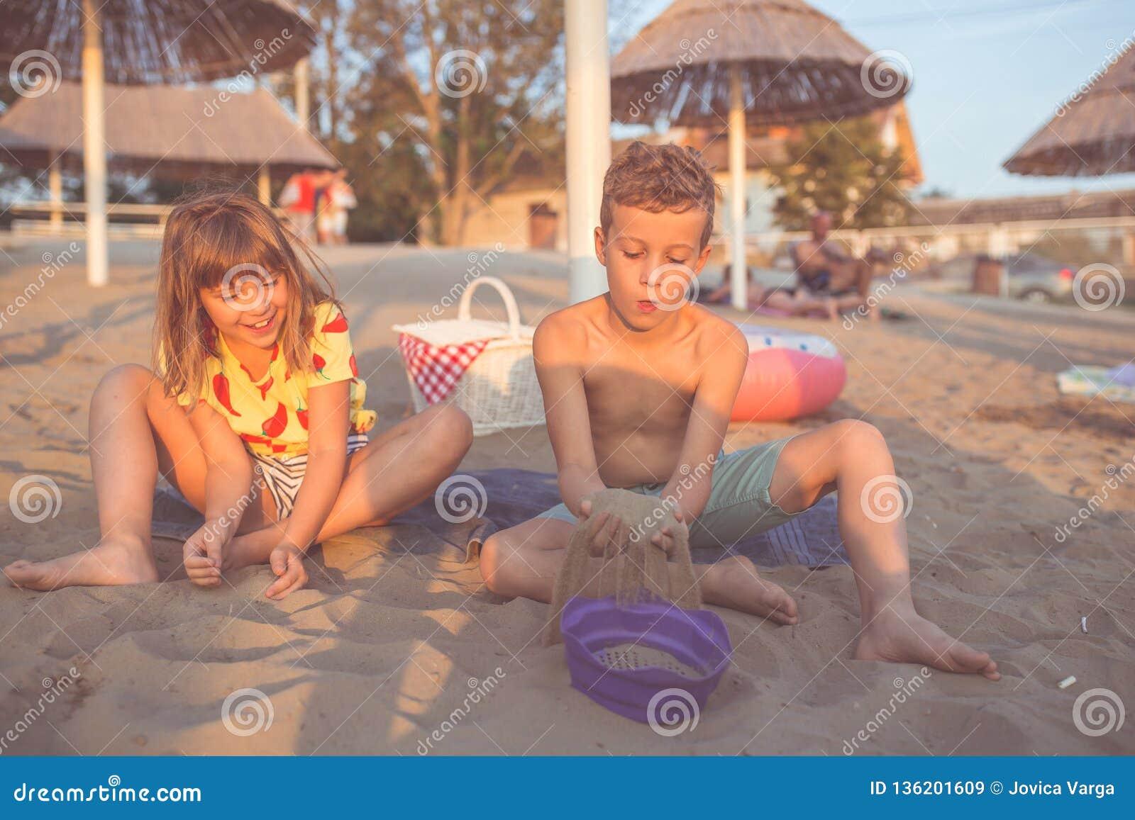 Niños felices y el jugar con la arena en la playa