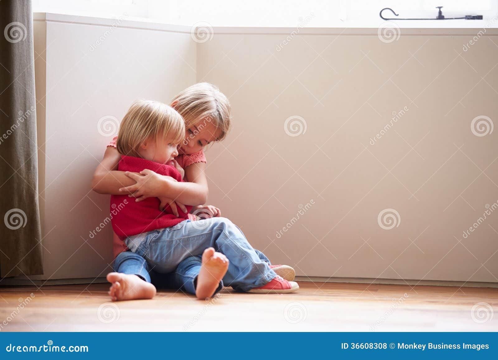 Niños infelices que se sientan en piso en esquina en casa