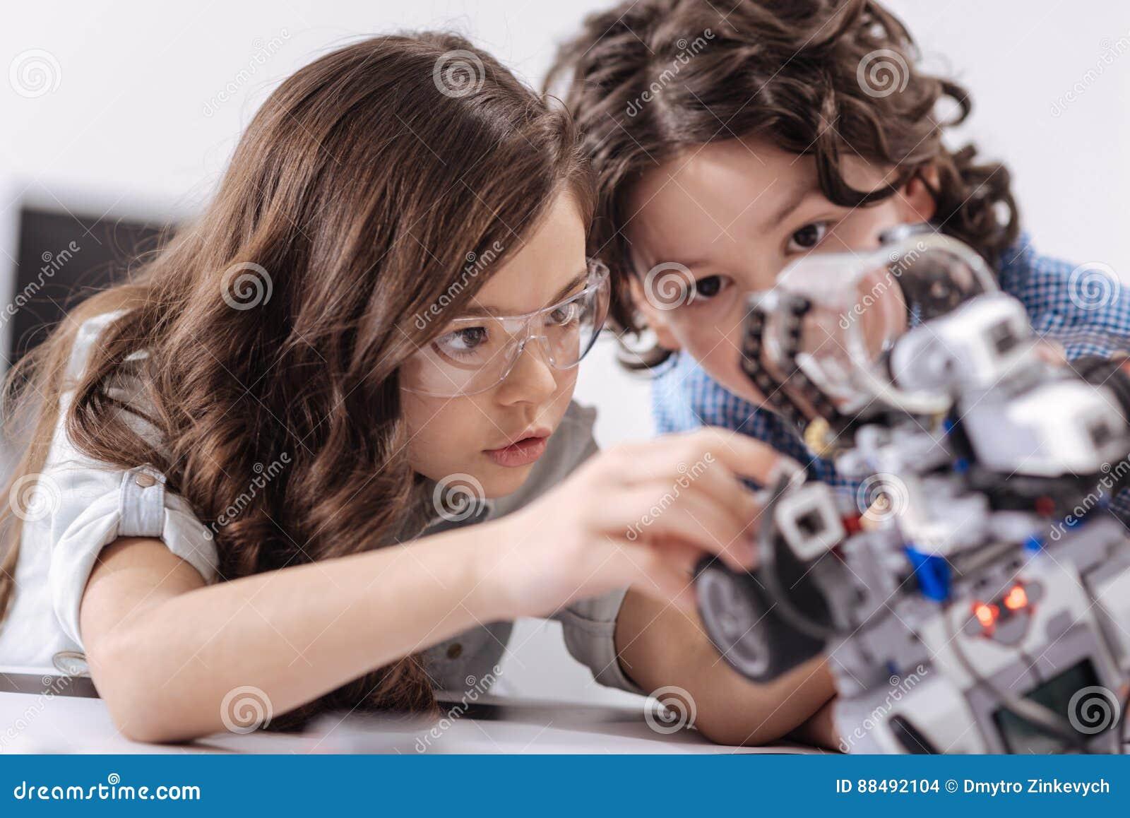 Niños inventivos que disfrutan de la lección de la ciencia en la escuela