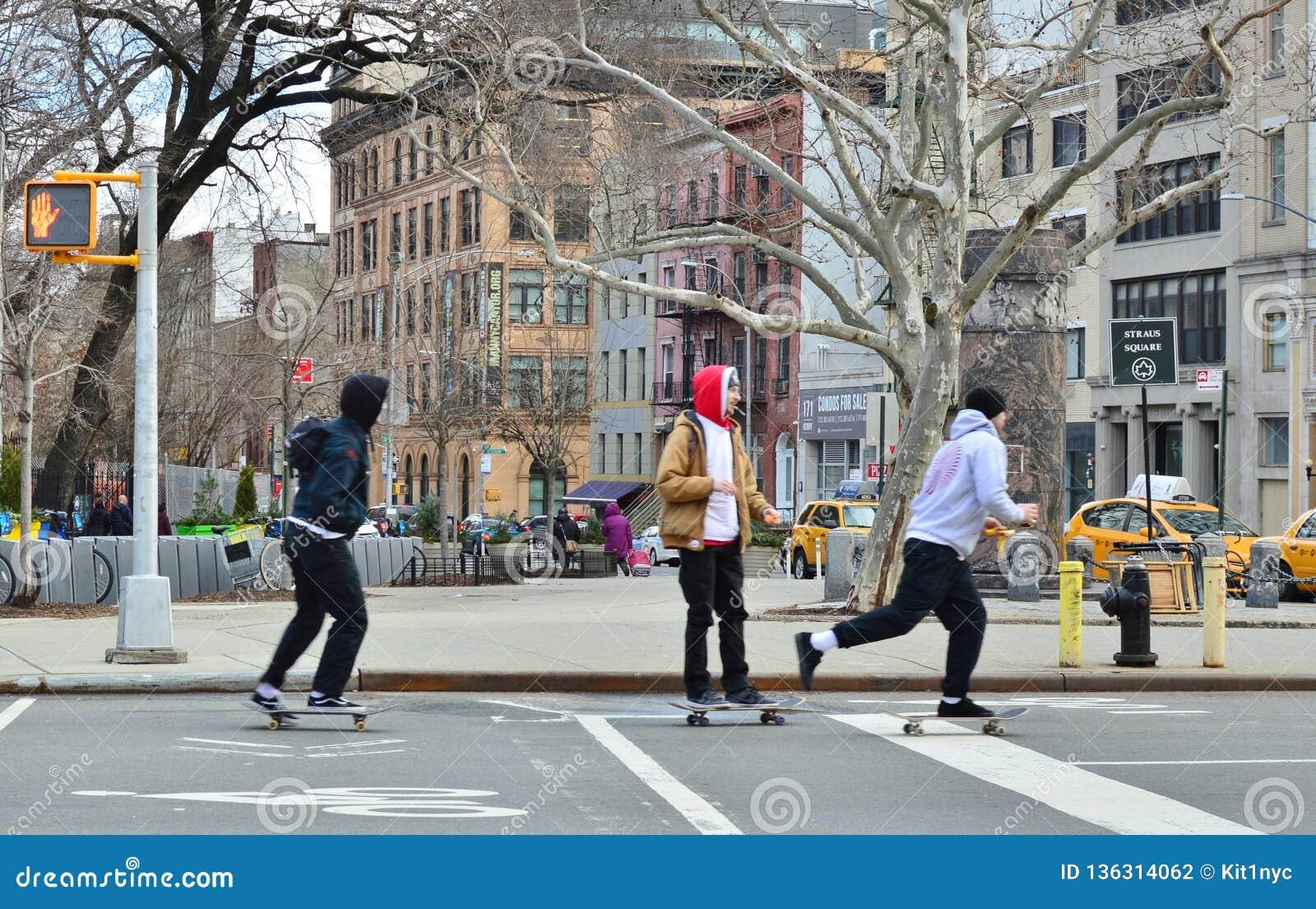 Niños jovenes del inconformista que montan el monopatín en centro de la ciudad del Lower East Side de Nueva York de las calles de