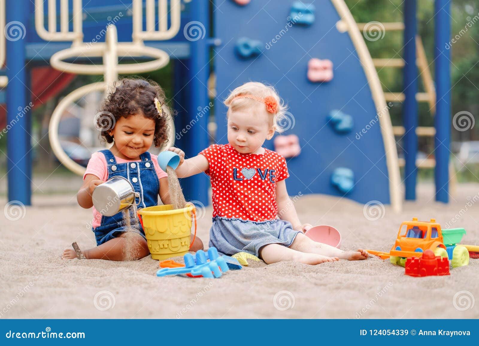 Niños latinos caucásicos e hispánicos de los bebés que se sientan en la salvadera que juega con los juguetes coloridos plásticos