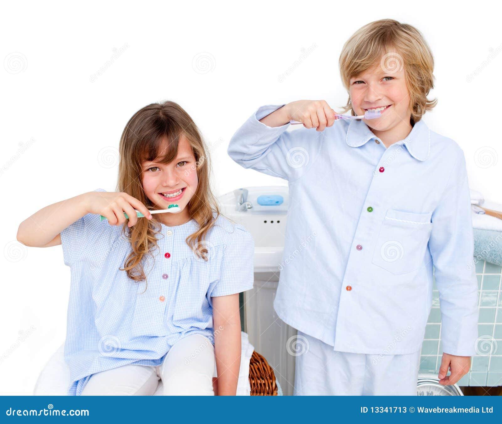 Niños lindos que aplican sus dientes con brocha