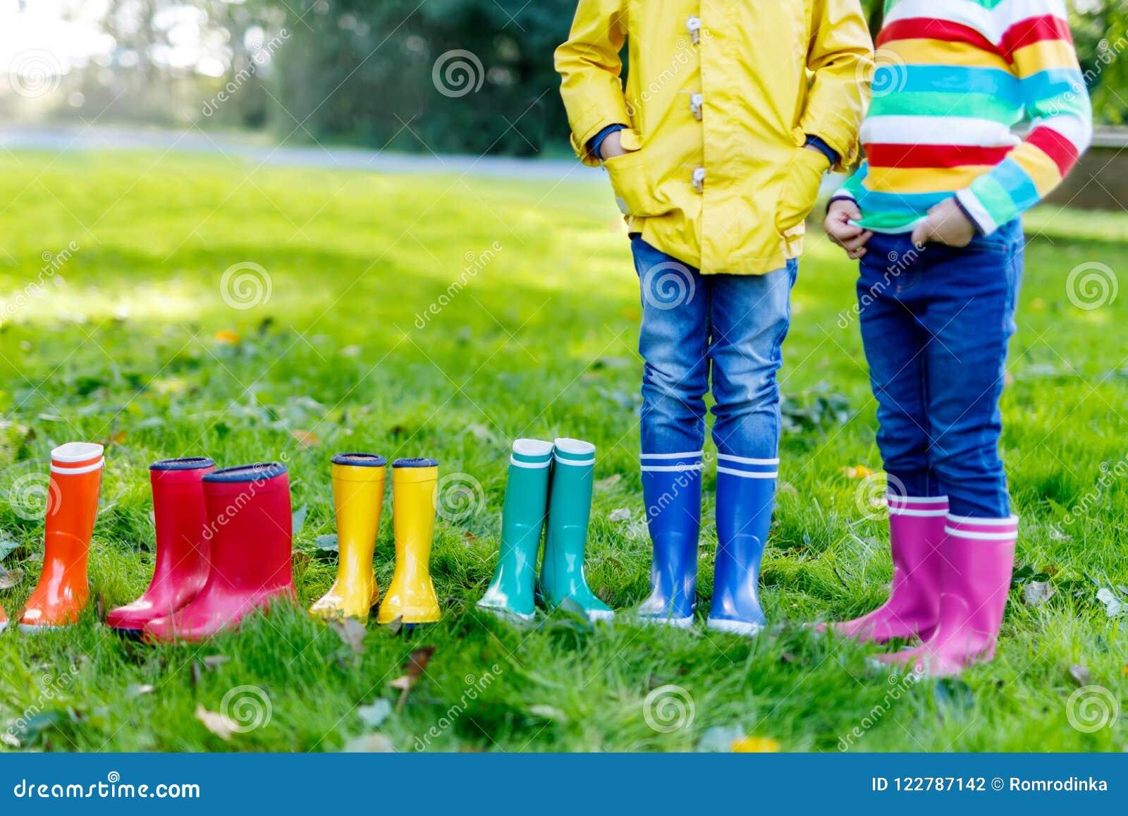 Niños, muchachos o muchachas en vaqueros y chaqueta amarilla en botas de lluvia coloridas