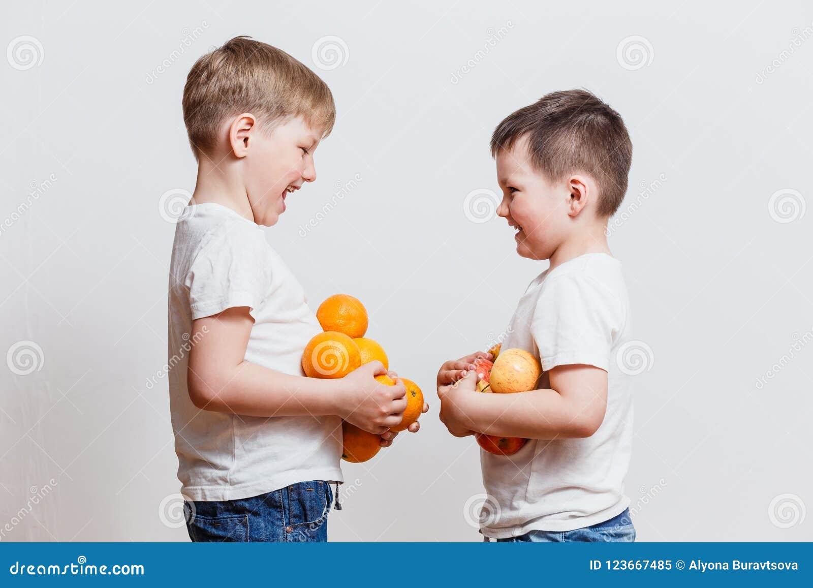 Niños pequeños en las camisetas blancas con la fruta a disposición