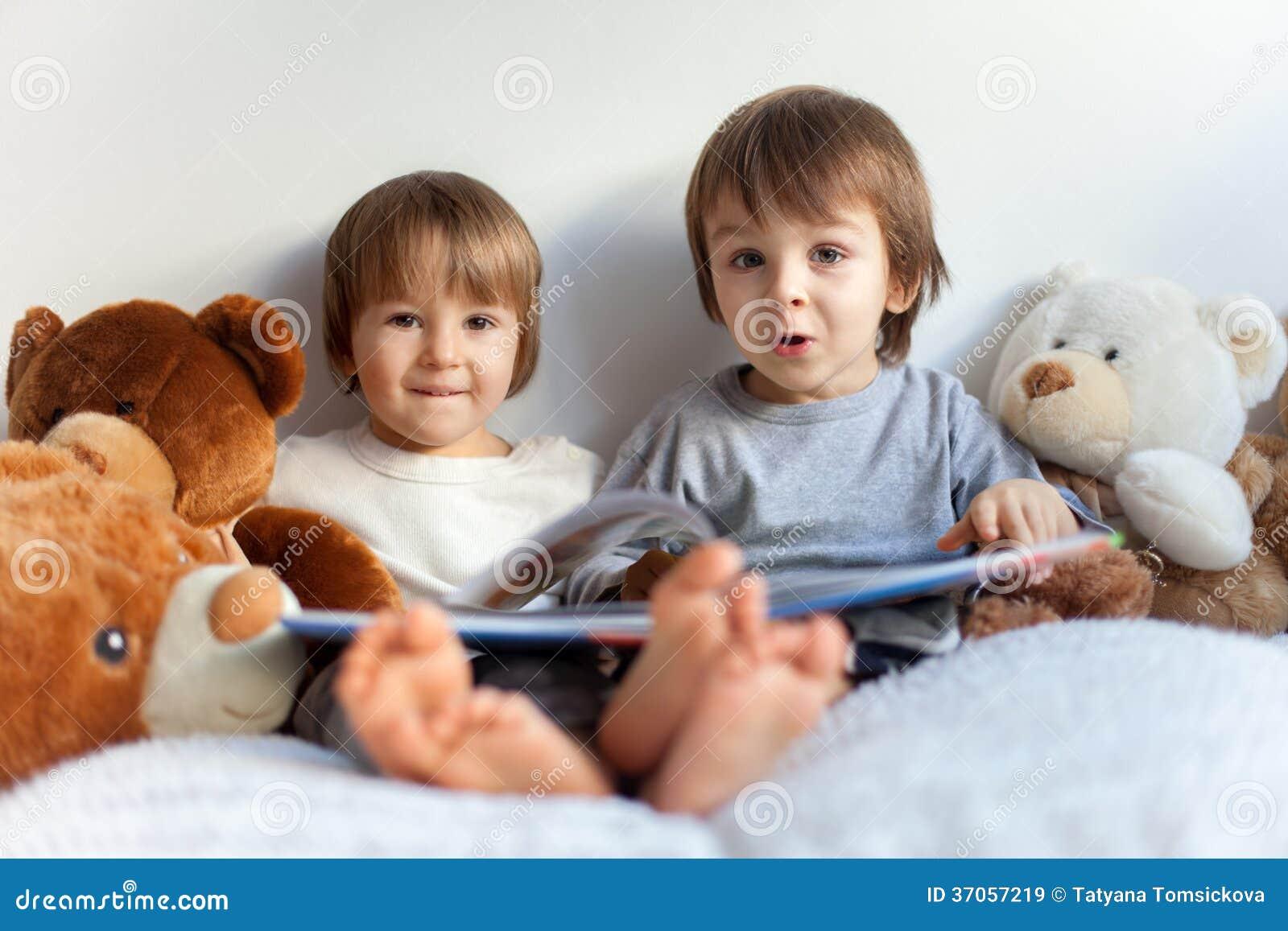 Ninos Pequenos Sentandose En La Cama Leyendo Un Libro Imagen De - Cama-para-nios-pequeos