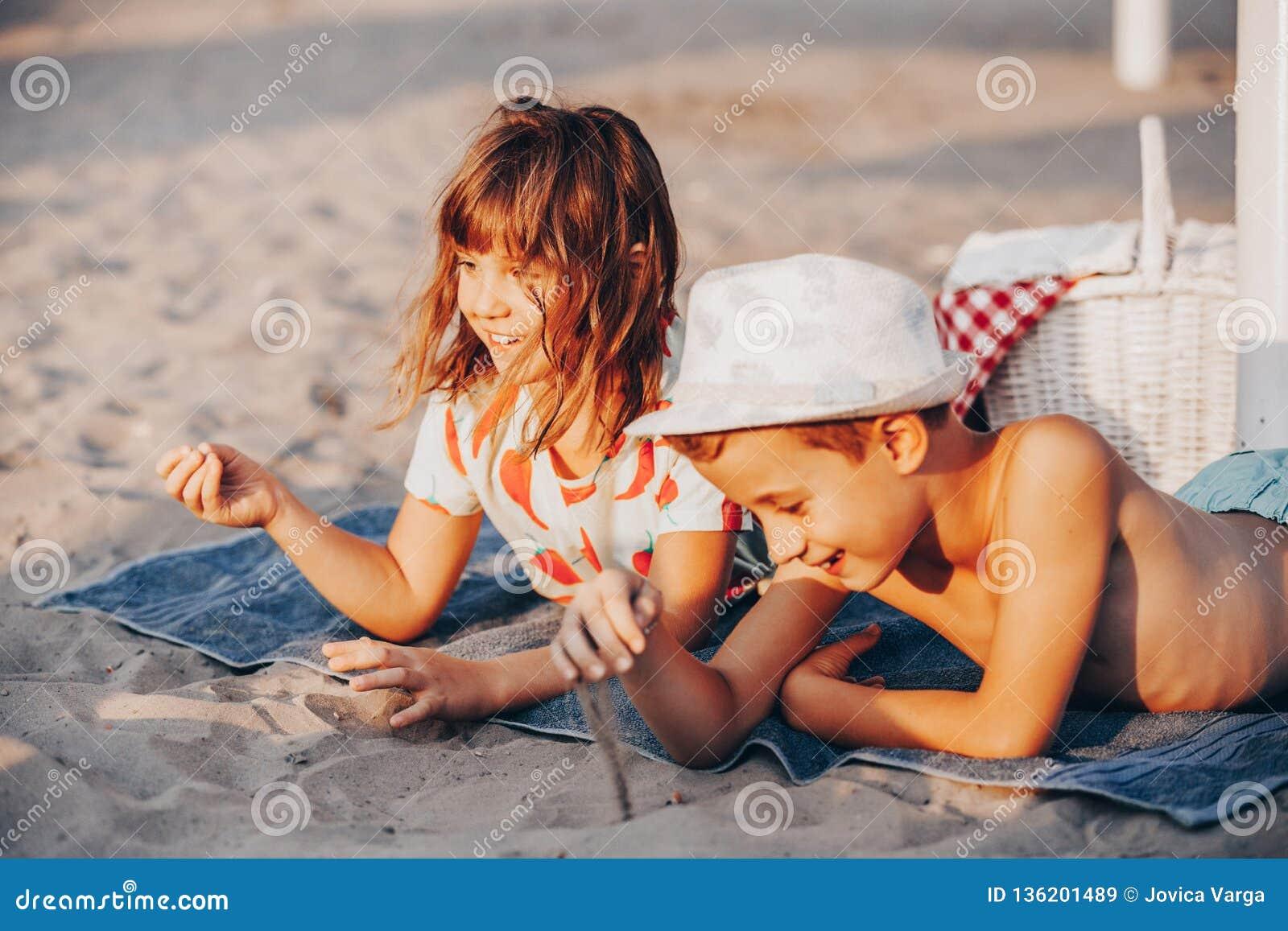 Niños positivos felices que juegan con la arena y hablar