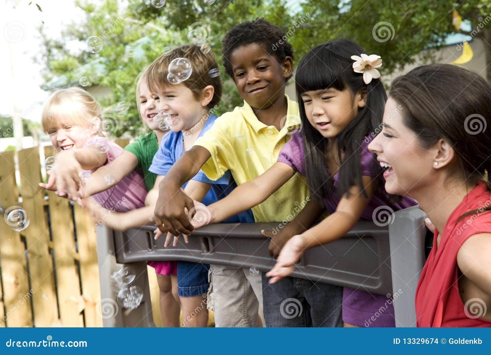 Niños preescolares en patio con el profesor