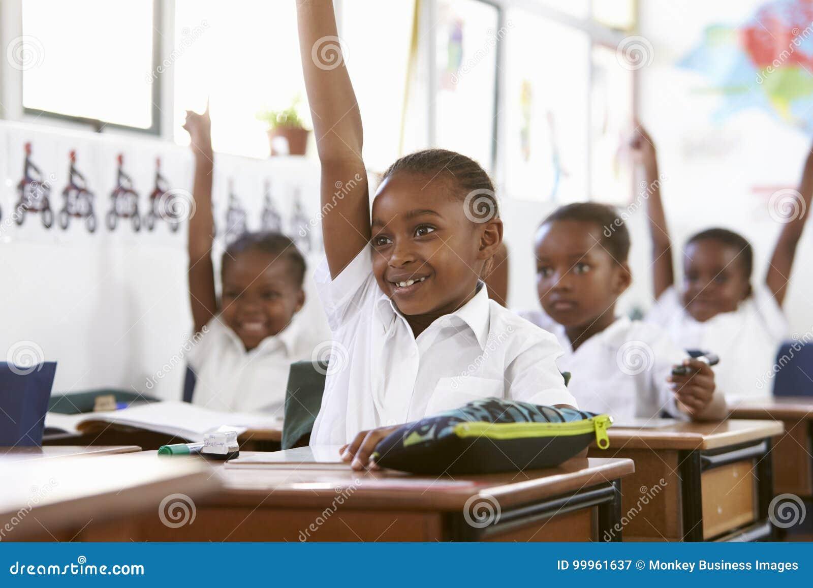 Niños que aumentan las manos durante una lección en una escuela primaria