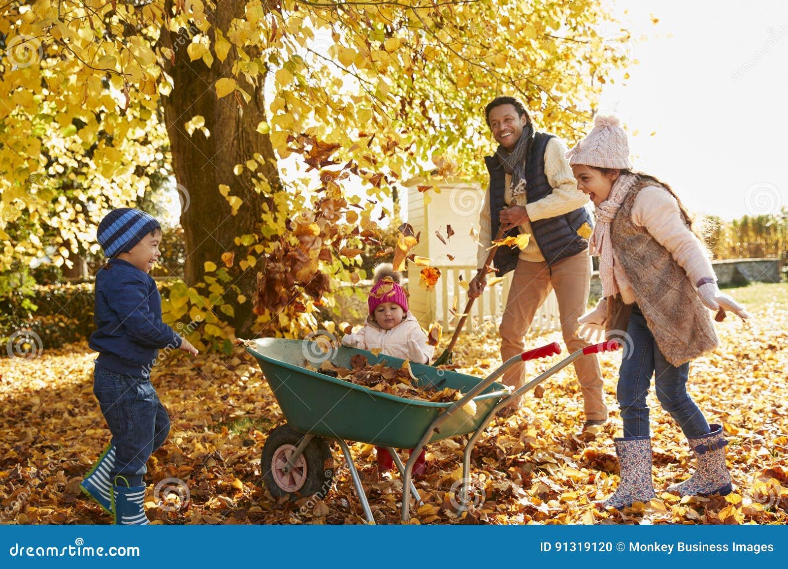 Niños que ayudan al padre To Collect Autumn Leaves In Garden