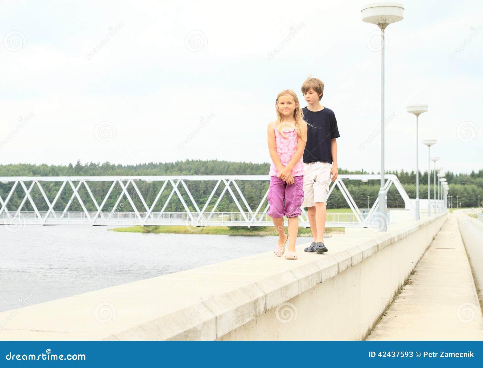 Niños que caminan en la verja de la presa