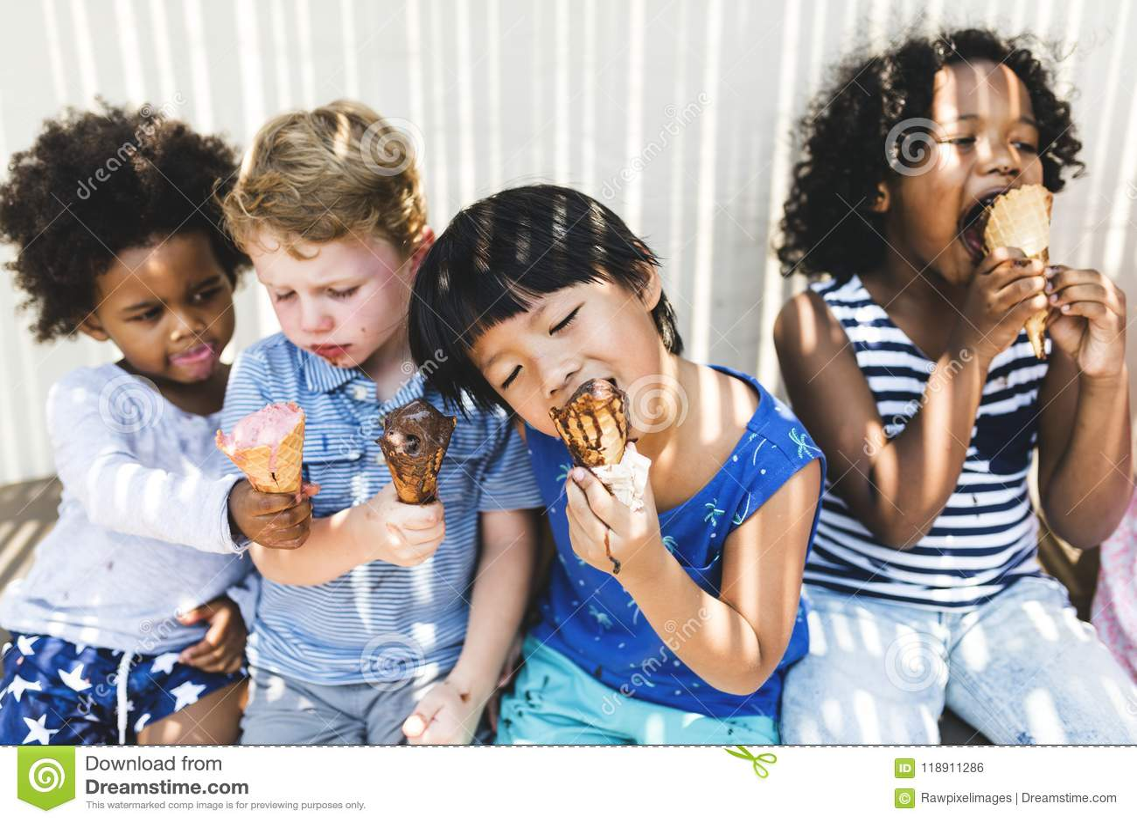 Niños que comen el helado delicioso