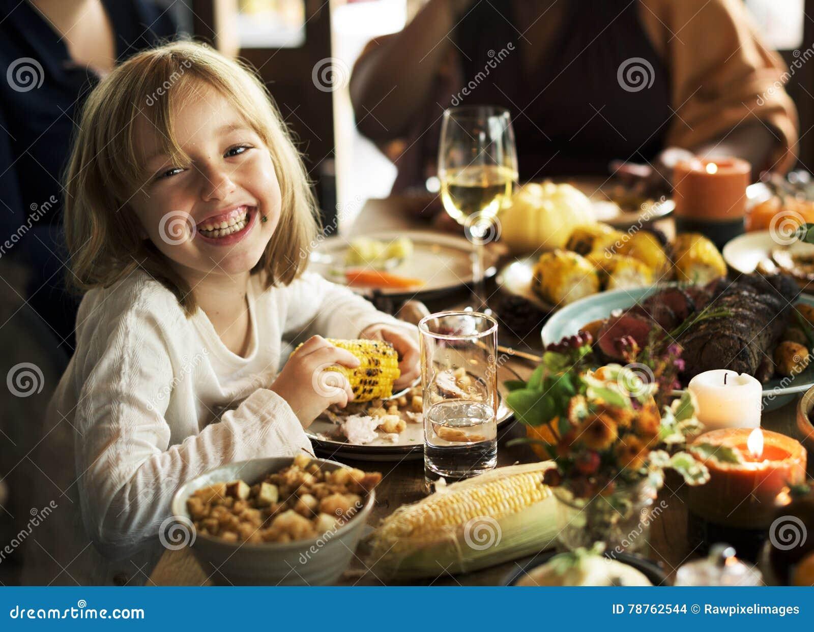 Niños que comen gozando de la comida en el concepto del partido de la acción de gracias
