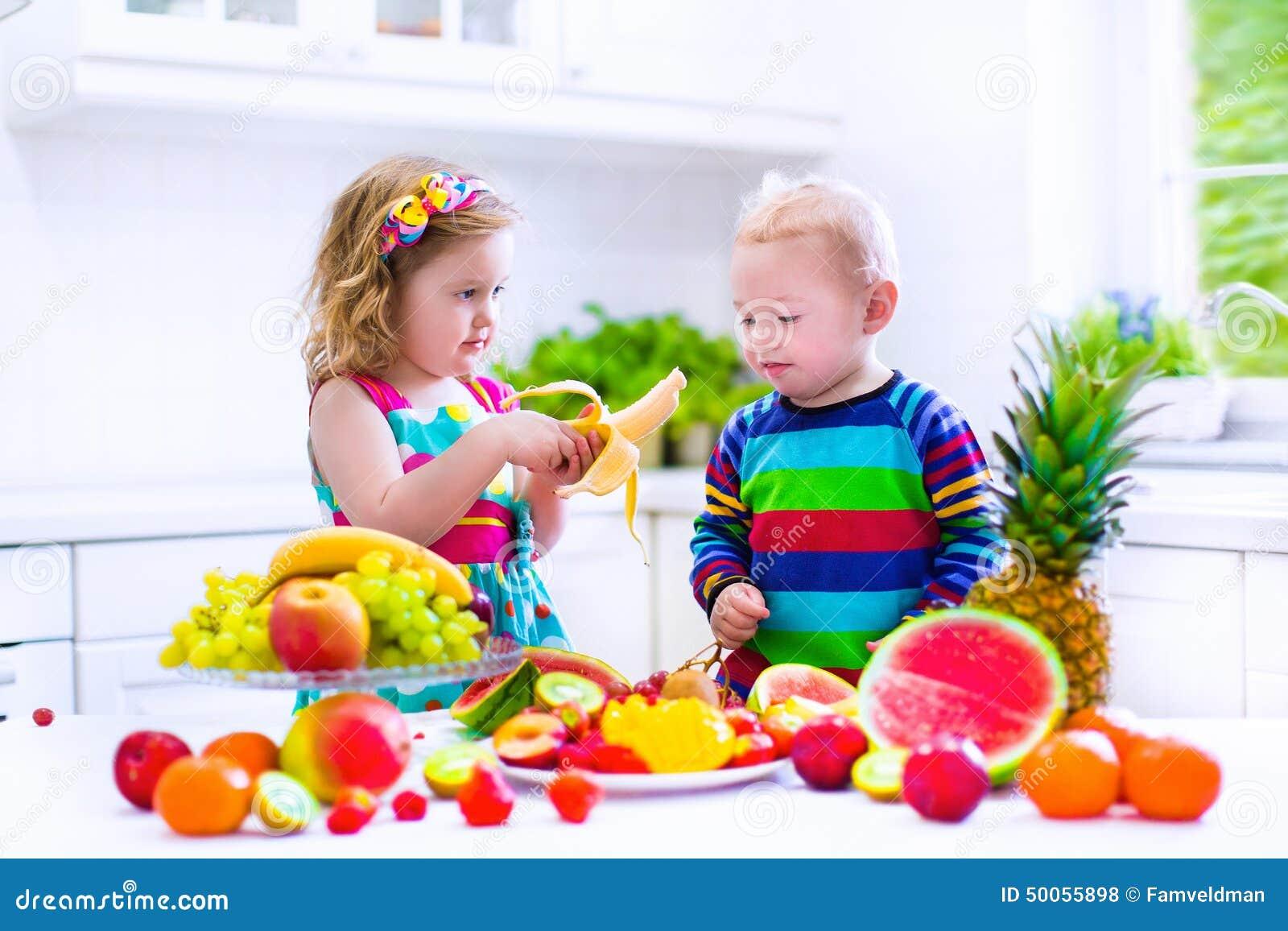 Niños Que Comen La Fruta En Una Cocina Blanca Foto De