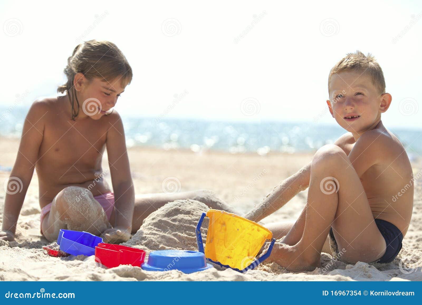 Niños que construyen el castillo de la arena en la playa