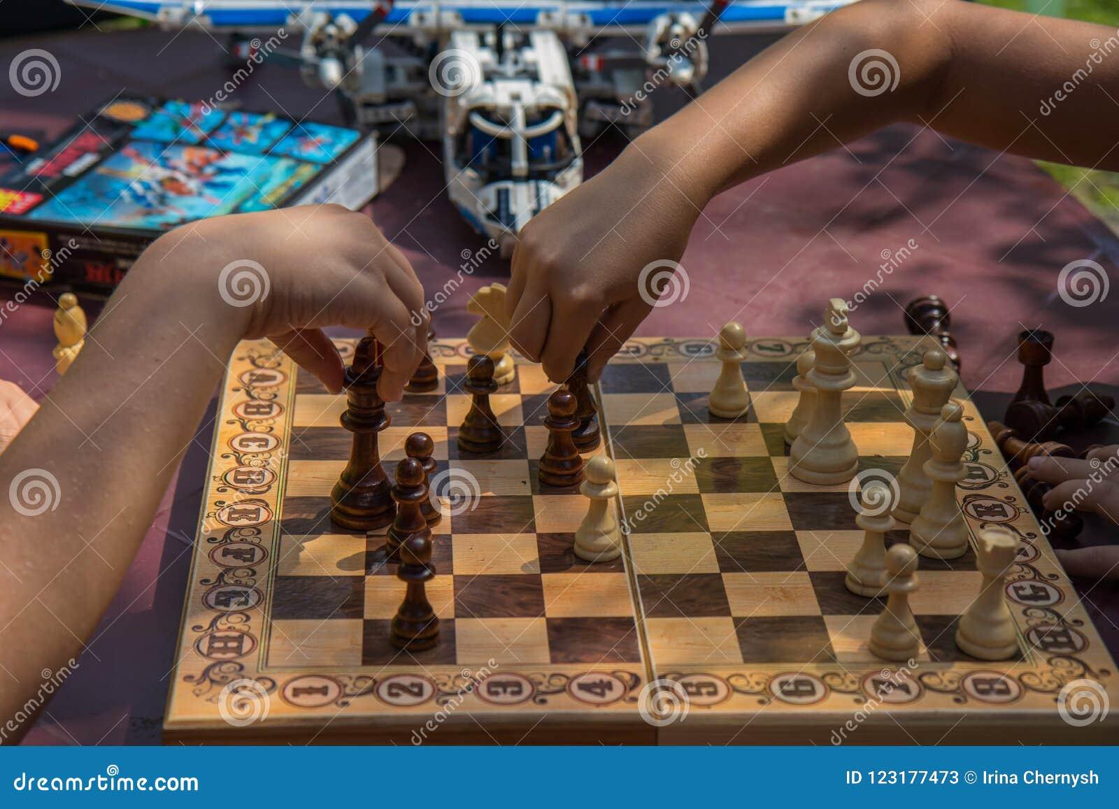 Niños que juegan a ajedrez en jardín con los juguetes borrosos en fondo