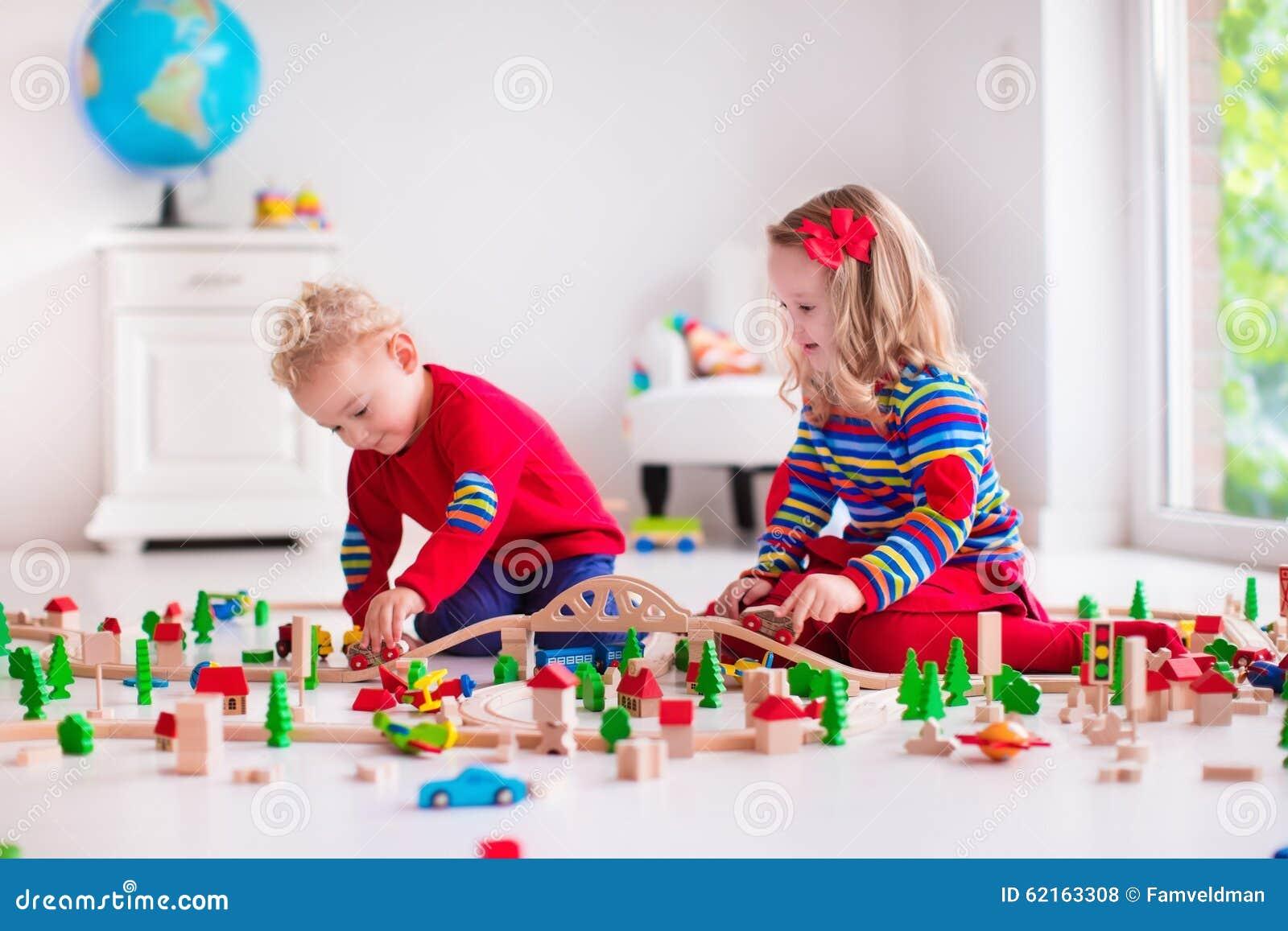 Niños que juegan con el ferrocarril y el tren del juguete