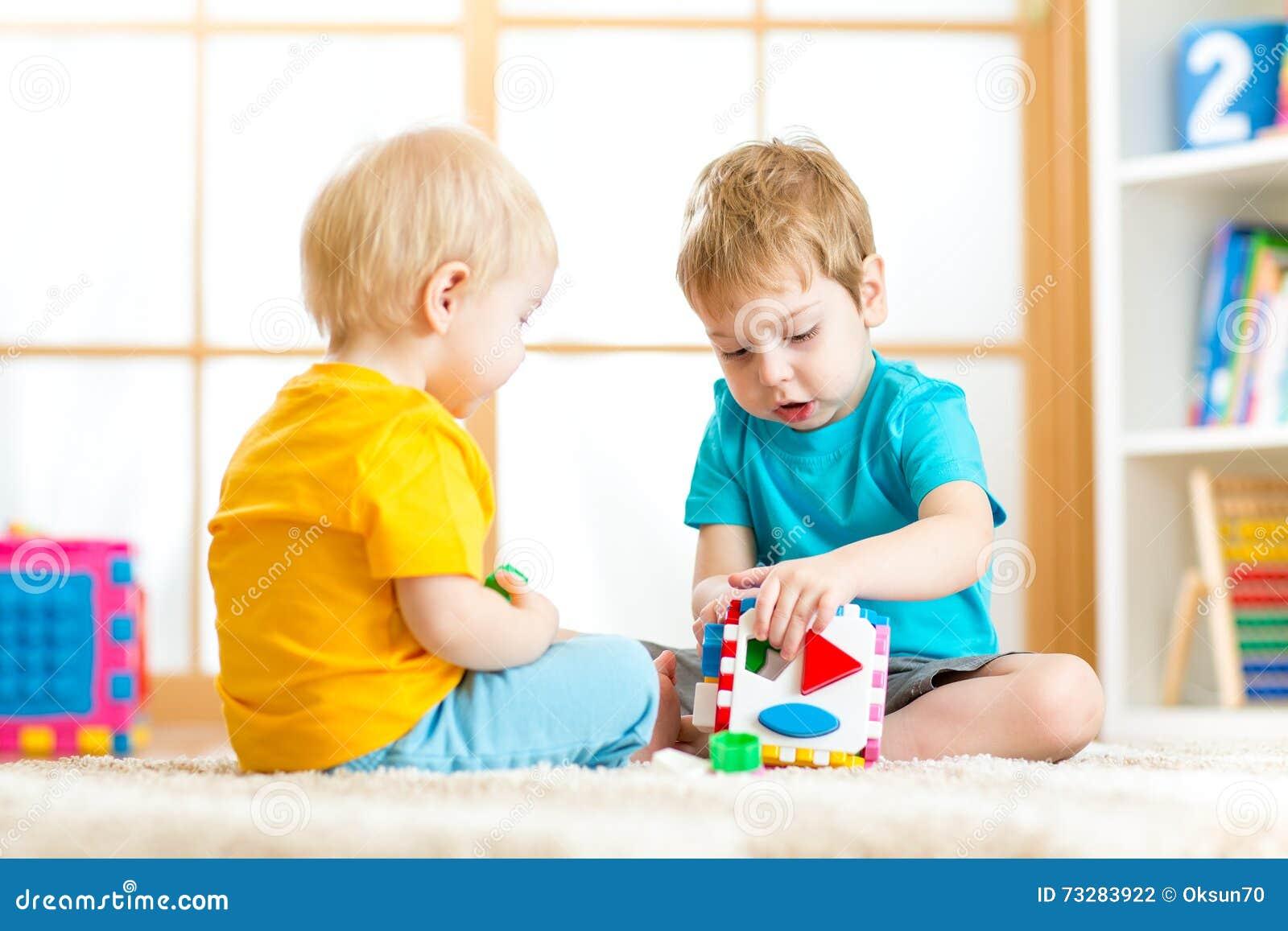 Niños que juegan con los juguetes educativos, arreglando y clasificando colores y formas Aprendizaje con el concepto de la experi