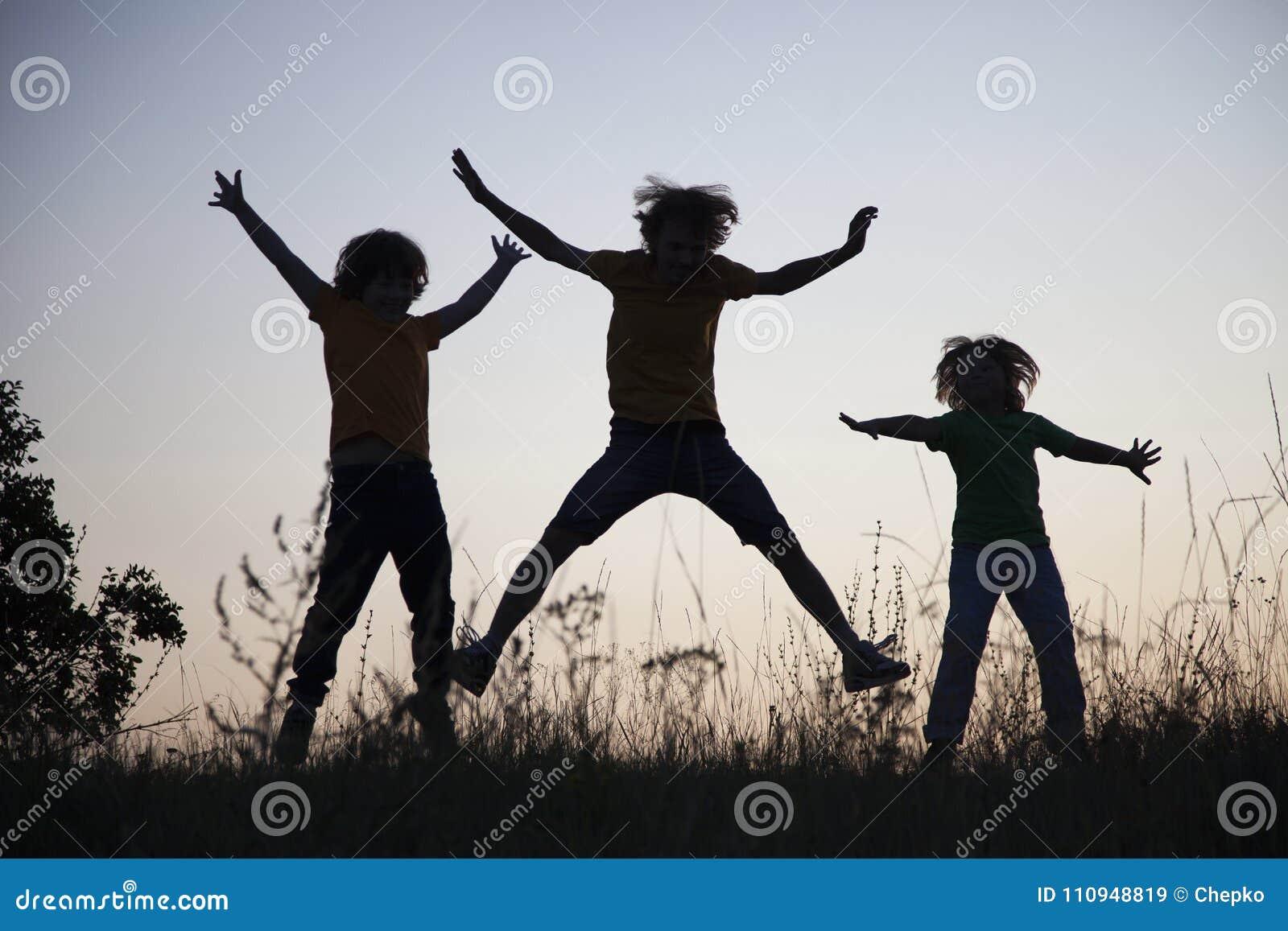 Niños que juegan el salto en el prado de la puesta del sol del verano silueteado