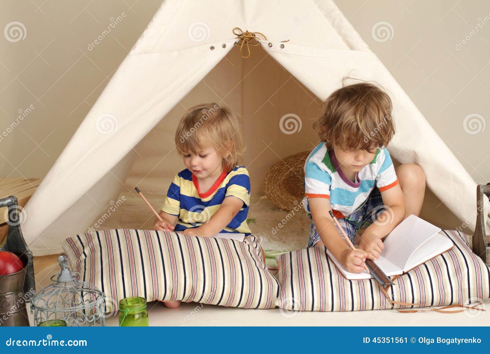 Niños que juegan en casa dentro con una tienda de la tienda de los indios norteamericanos