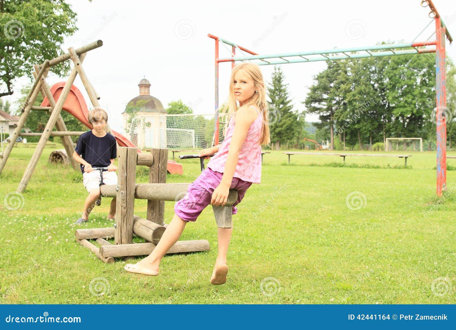 Niños que juegan en el oscilación de madera