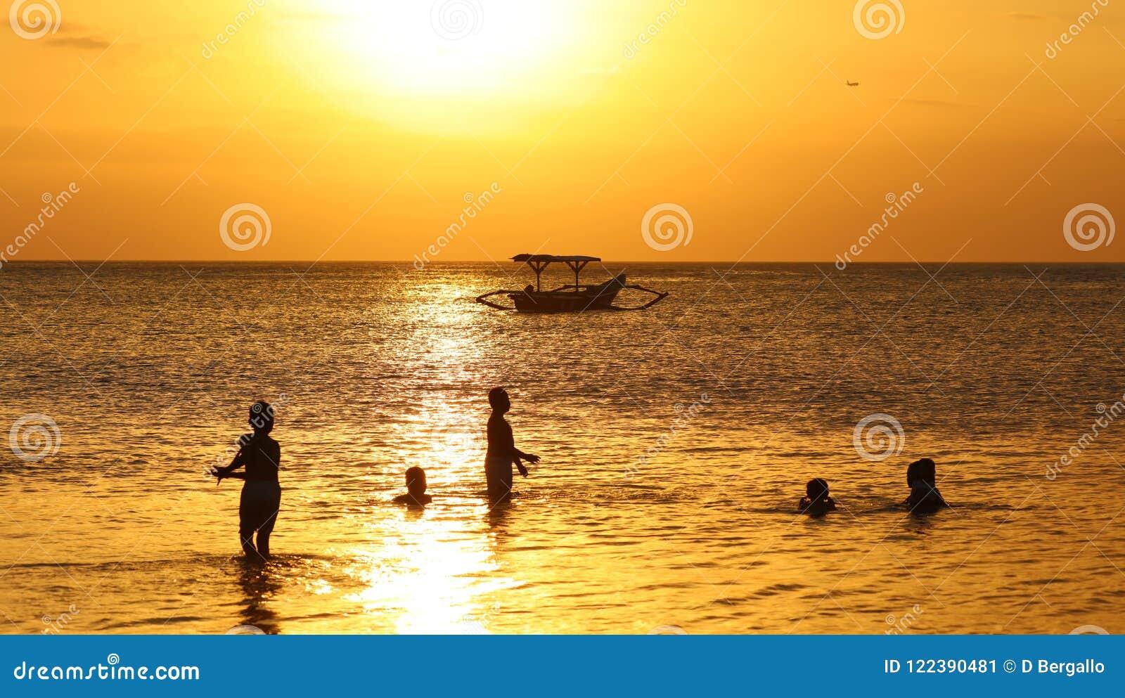 Niños que juegan en la playa con el barco en Bali, Indonesia del pescador durante puesta del sol en la playa