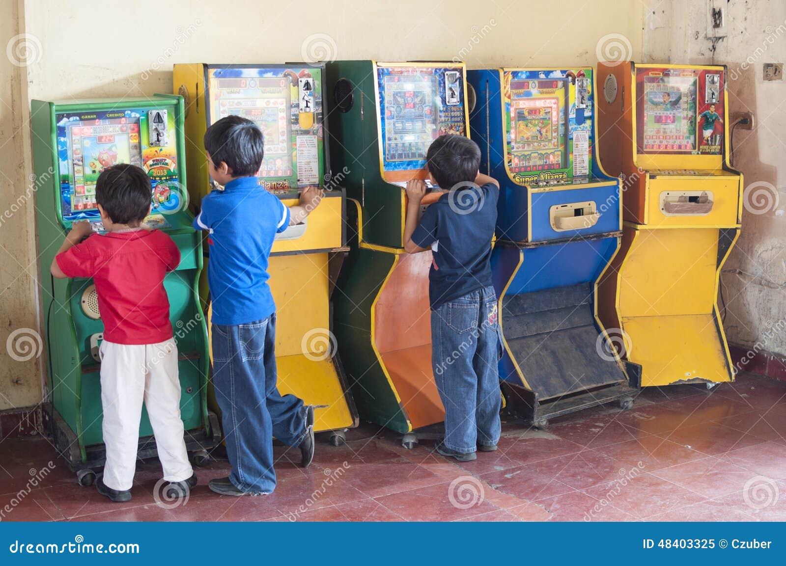 Ninos Que Juegan A Juegos De Arcada Del Bingo Imagen Editorial