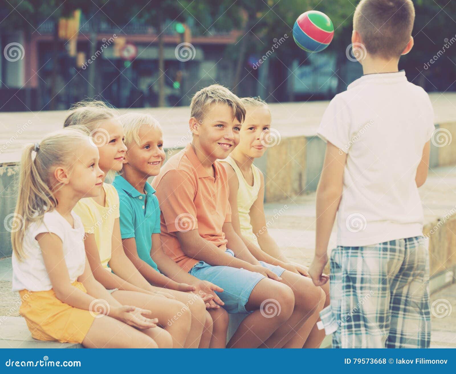 Niños que juegan la bola junto