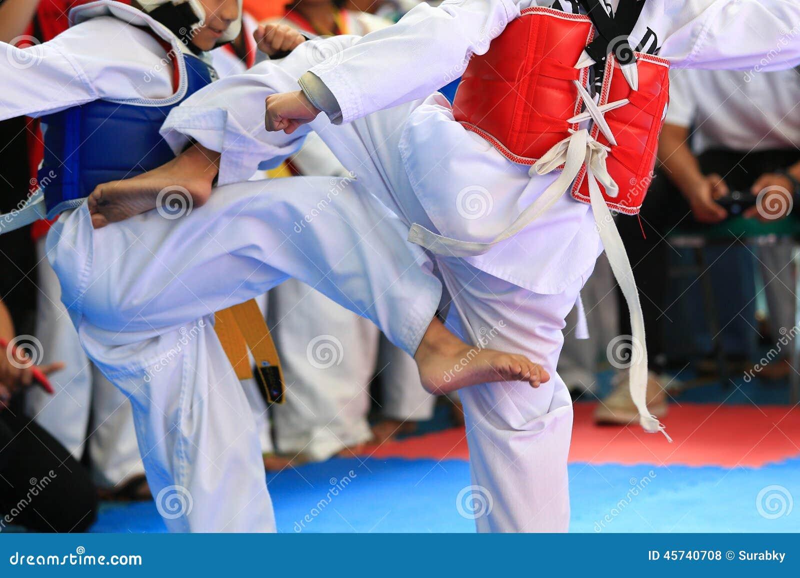 Niños que luchan en etapa durante la competencia del Taekwondo