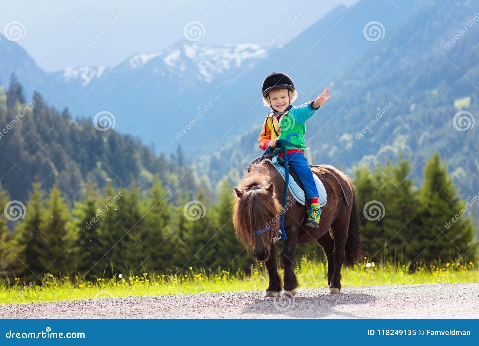 Niños que montan el potro Niño en caballo en montañas de las montañas