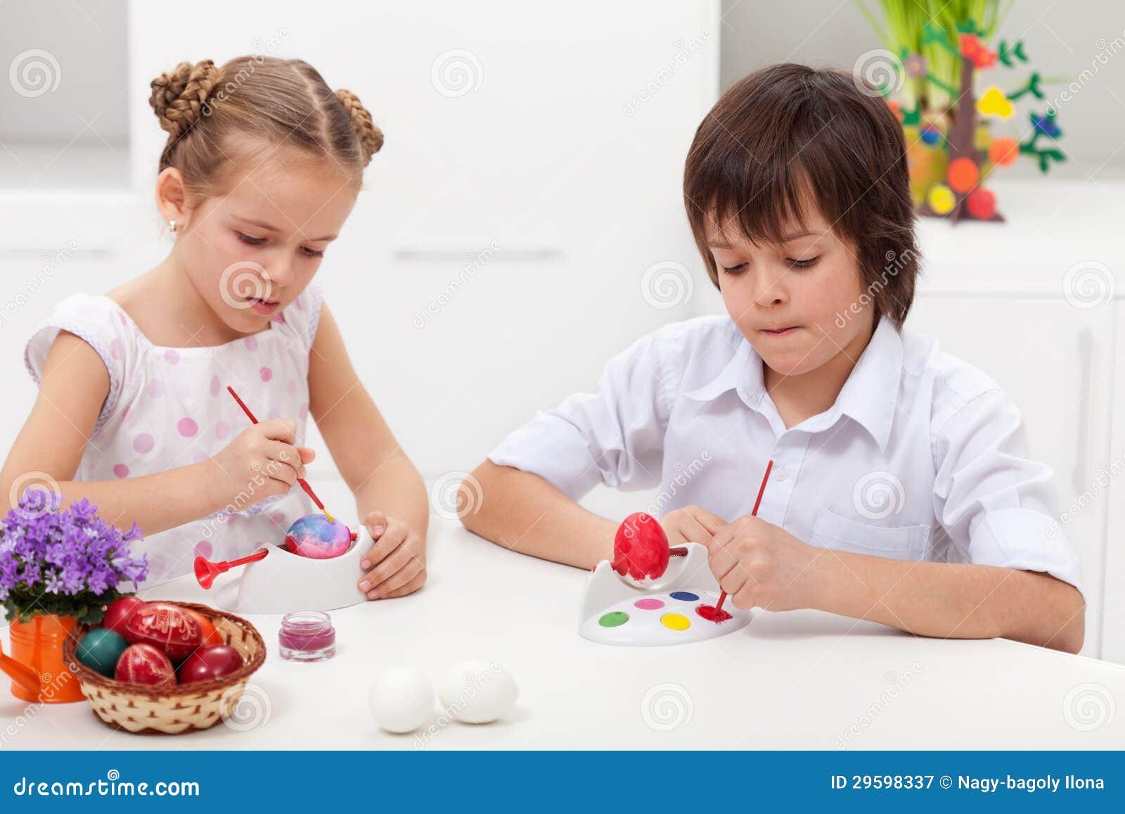 Niños que pintan los huevos de Pascua