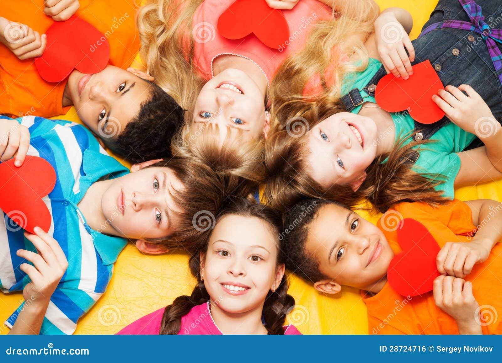 Niños que ponen en círculo con los corazones en sus manos