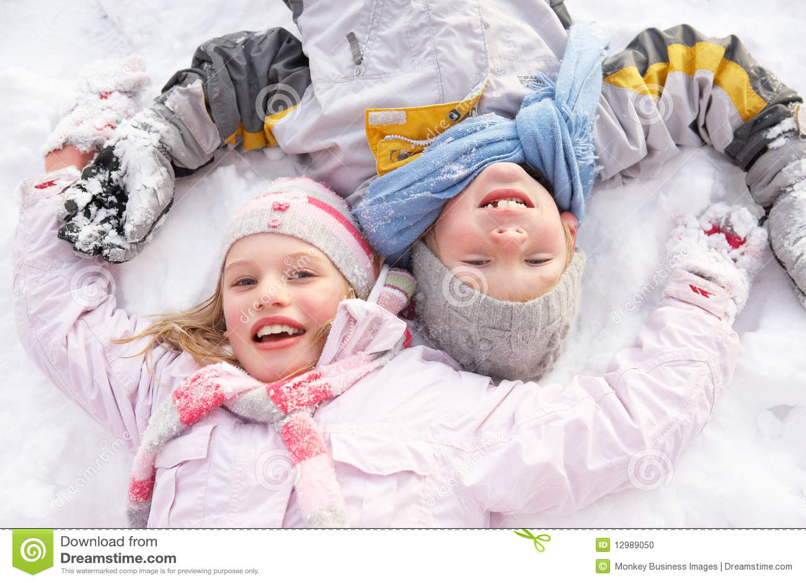 Niños que ponen en el ángel de fabricación de tierra de la nieve
