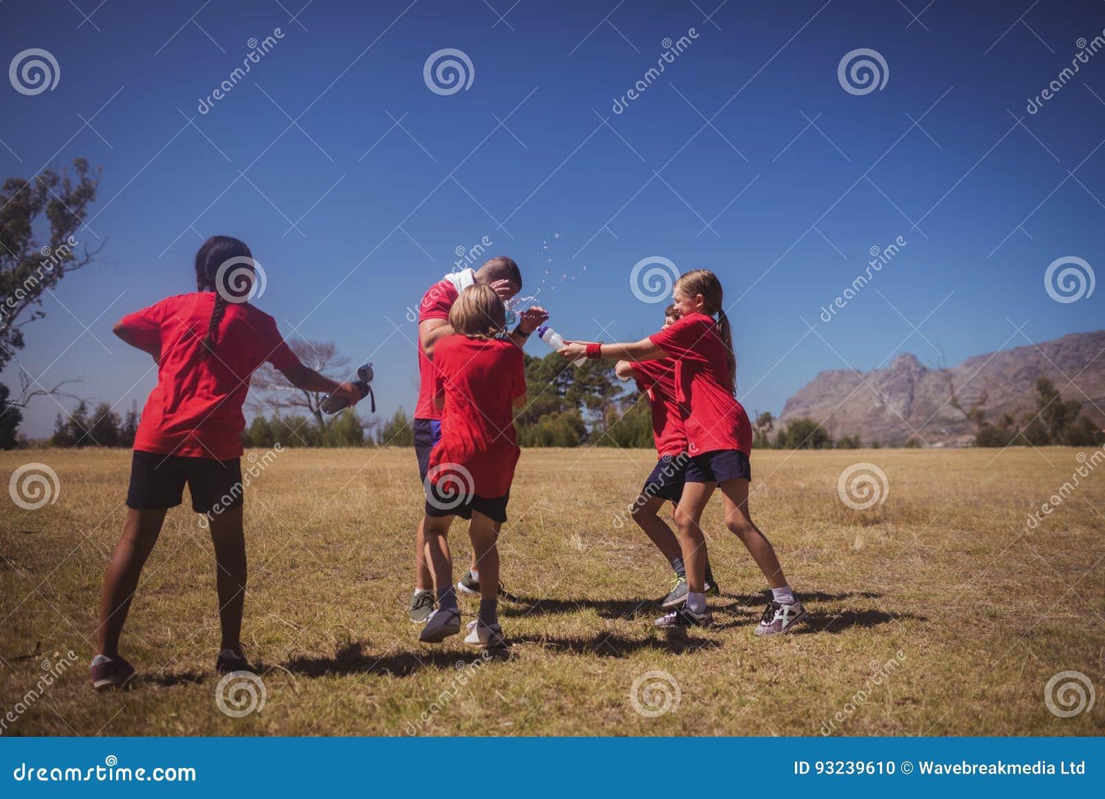 Niños que se divierten con el instructor en el campo de bota