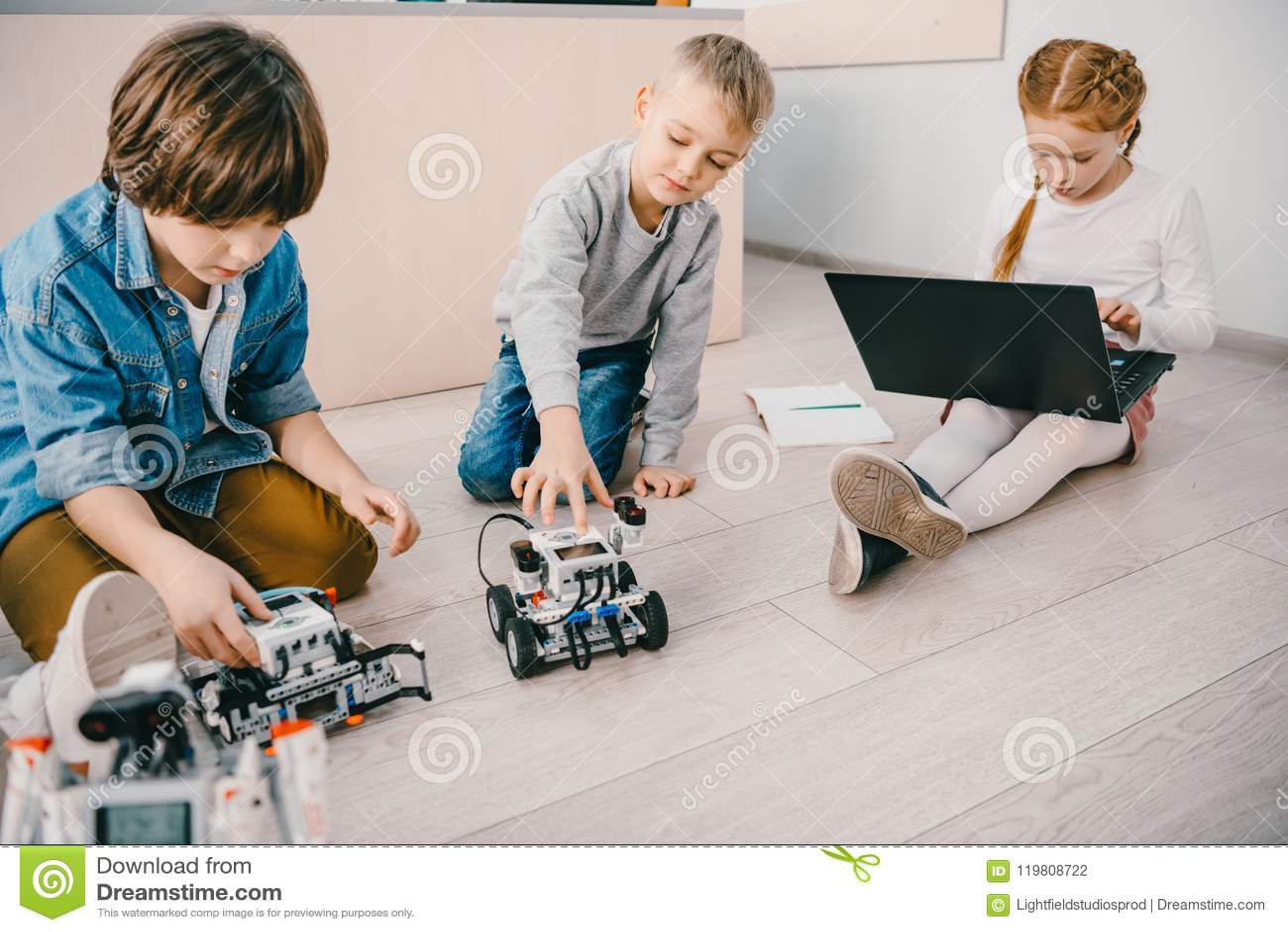 Niños que se sientan en piso en la clase de la educación del tronco con los robots