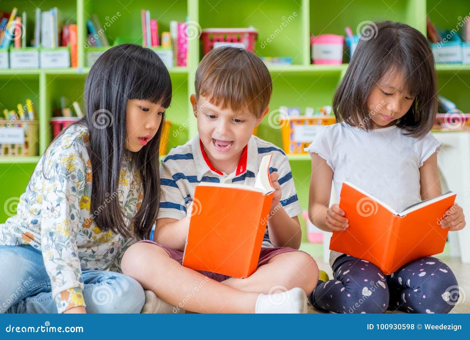 Niños que se sientan en piso y que leen el libro del cuento en li preescolar