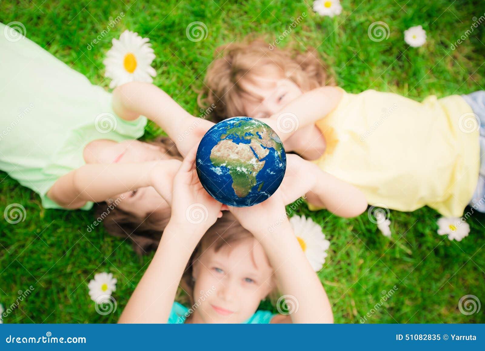 Niños que sostienen el planeta de la tierra en manos