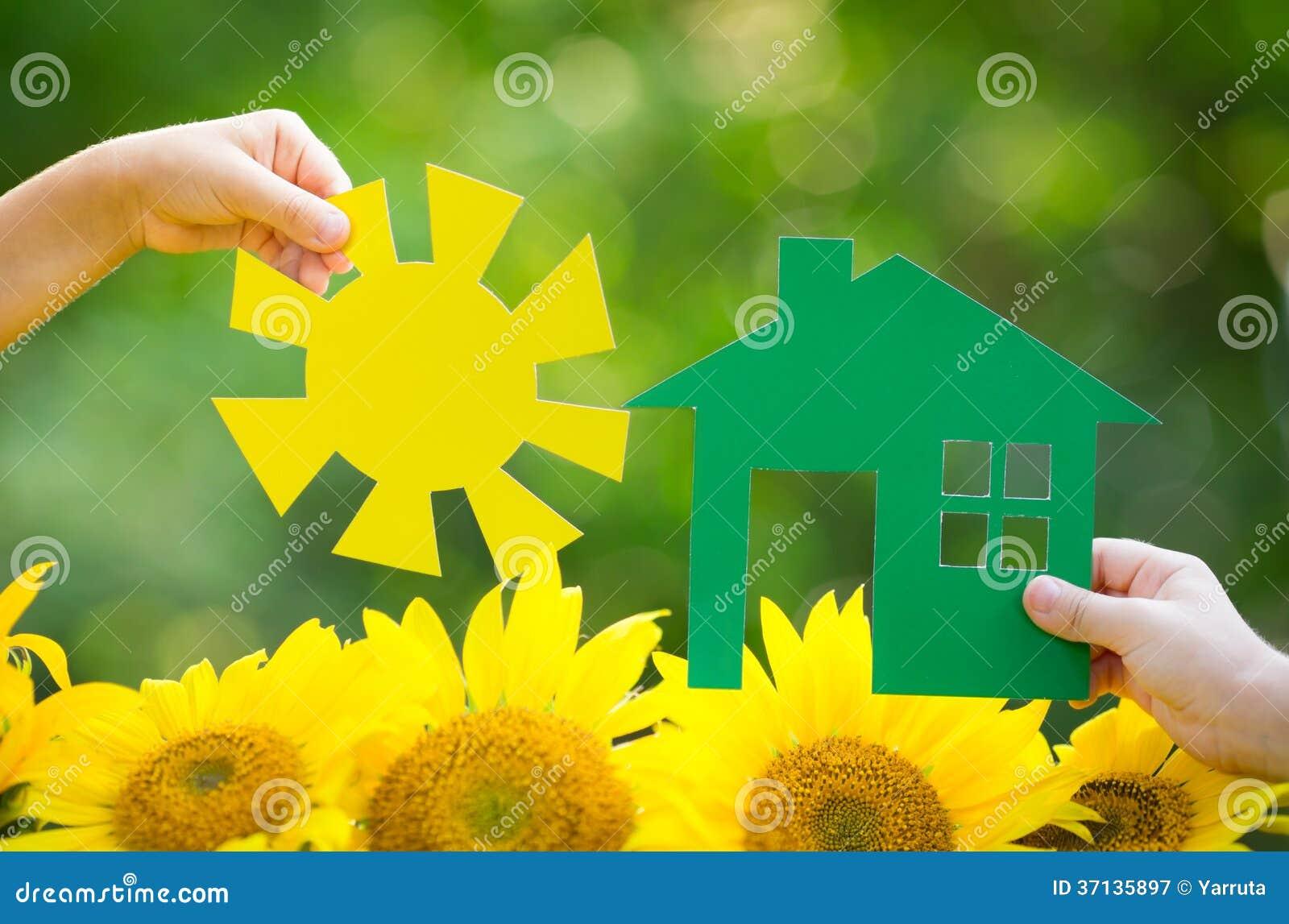 Niños que sostienen la casa y el sol de papel