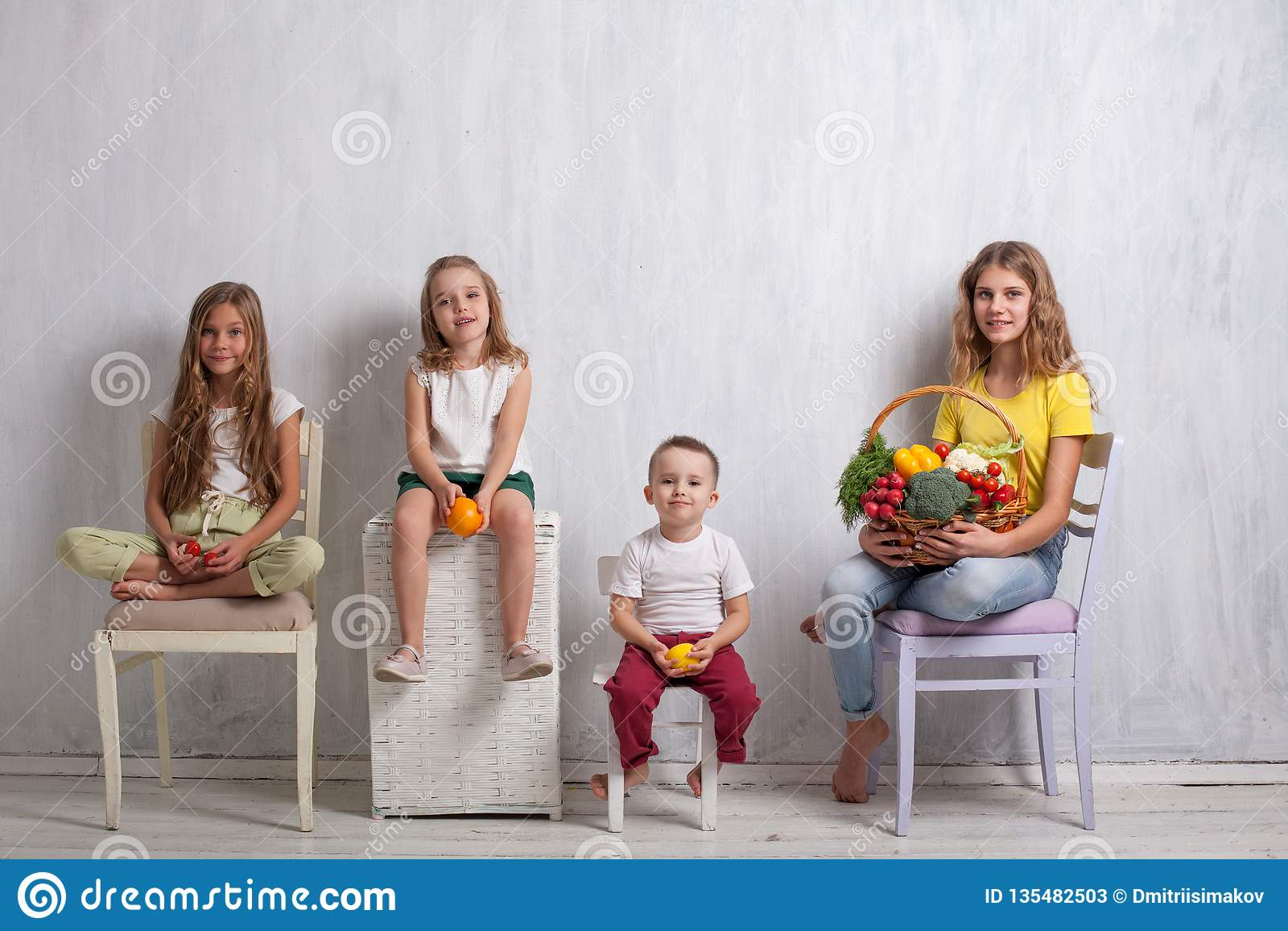 Niños que sostienen una cesta de comida sana de la fruta y verdura fresca