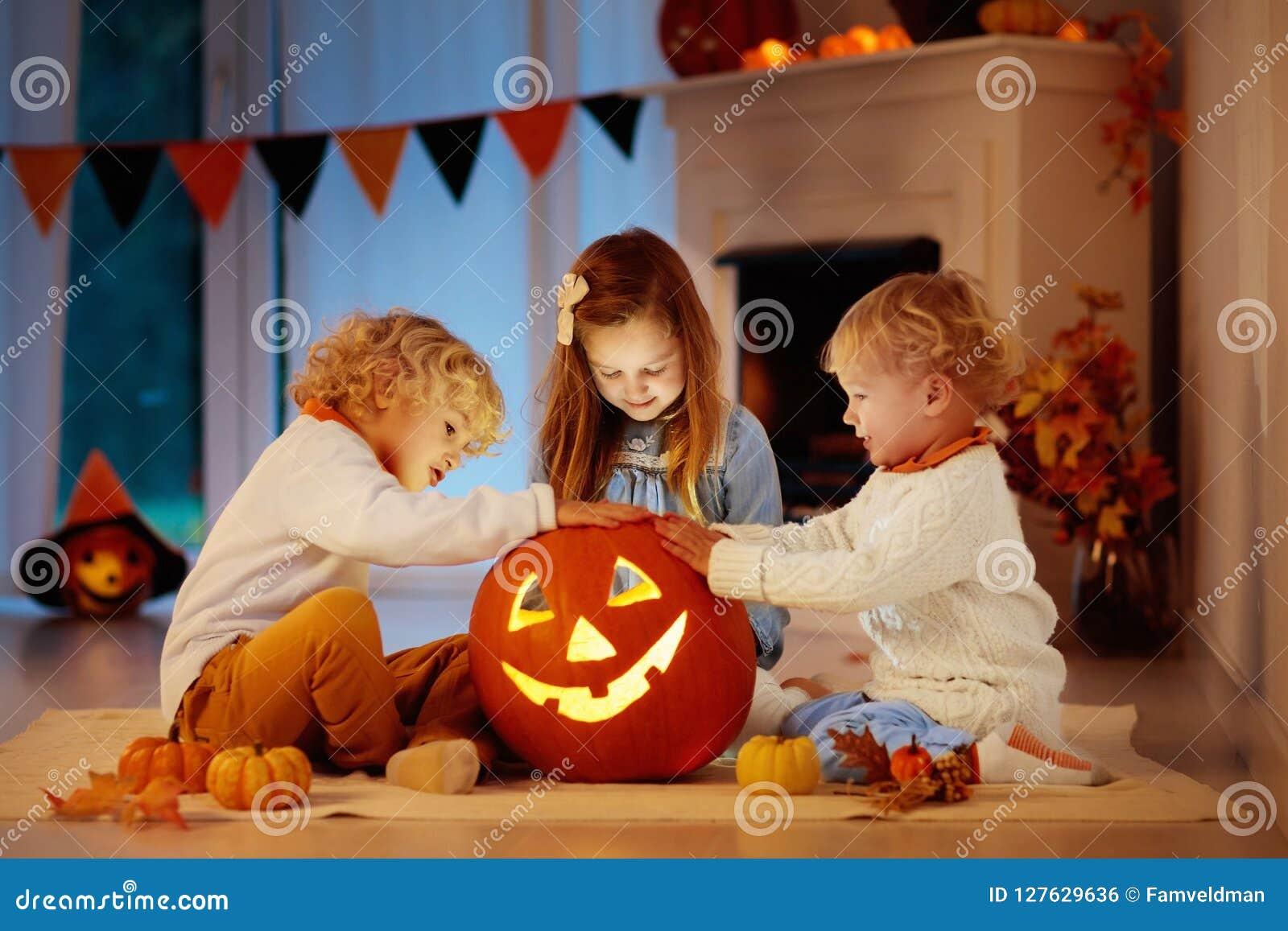 Niños que tallan la calabaza en Halloween Truco o convite